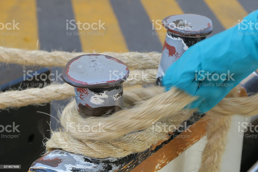 Worker's hands  tying up a boat, vaperetto,  to the dock stock photo