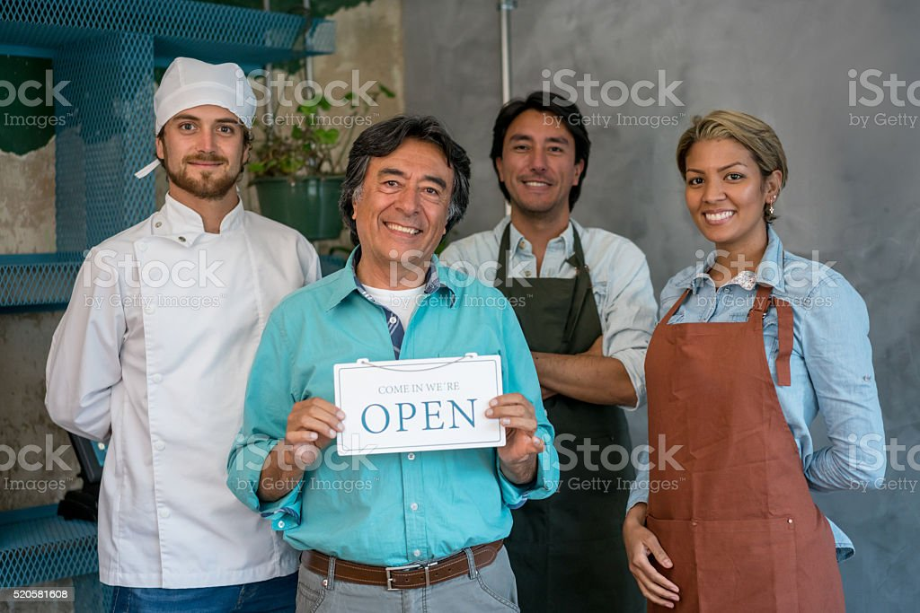 Workers holding an open sign at a restaurant stock photo