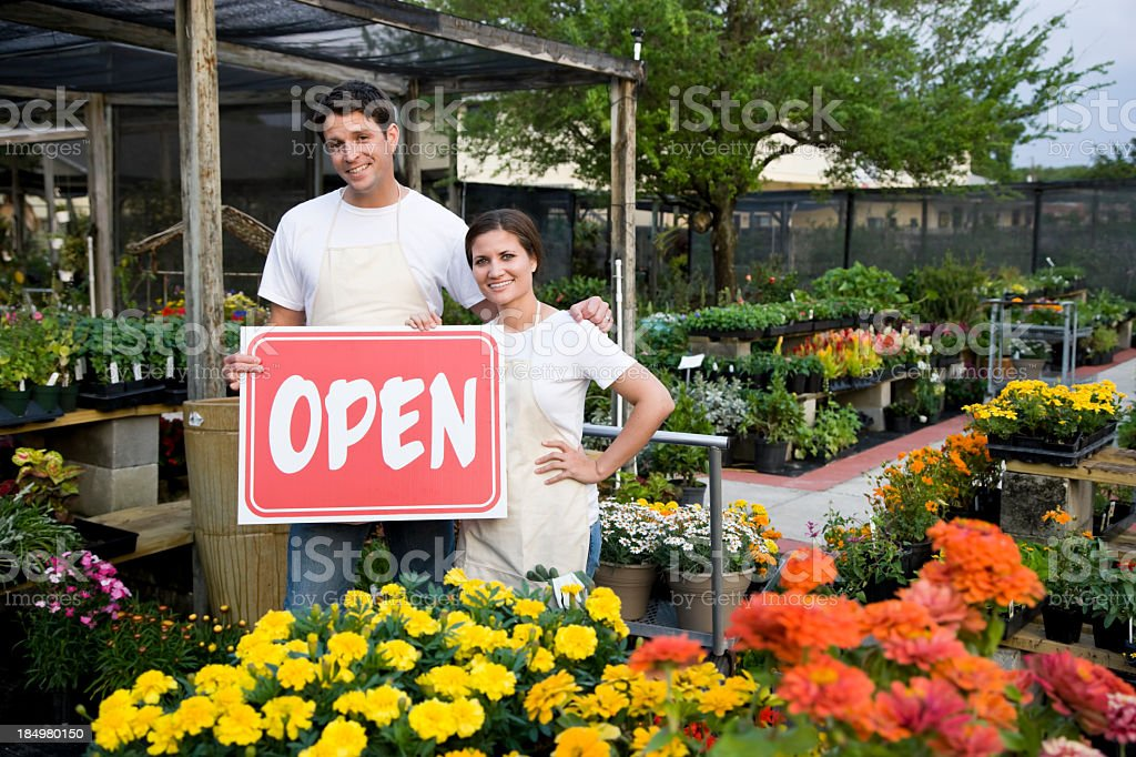 Workers holding OPEN sign outside a plant nursery royalty-free stock photo
