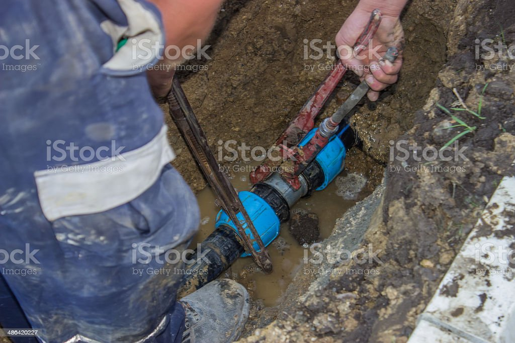 workers holds wrench and in trench 2 stock photo