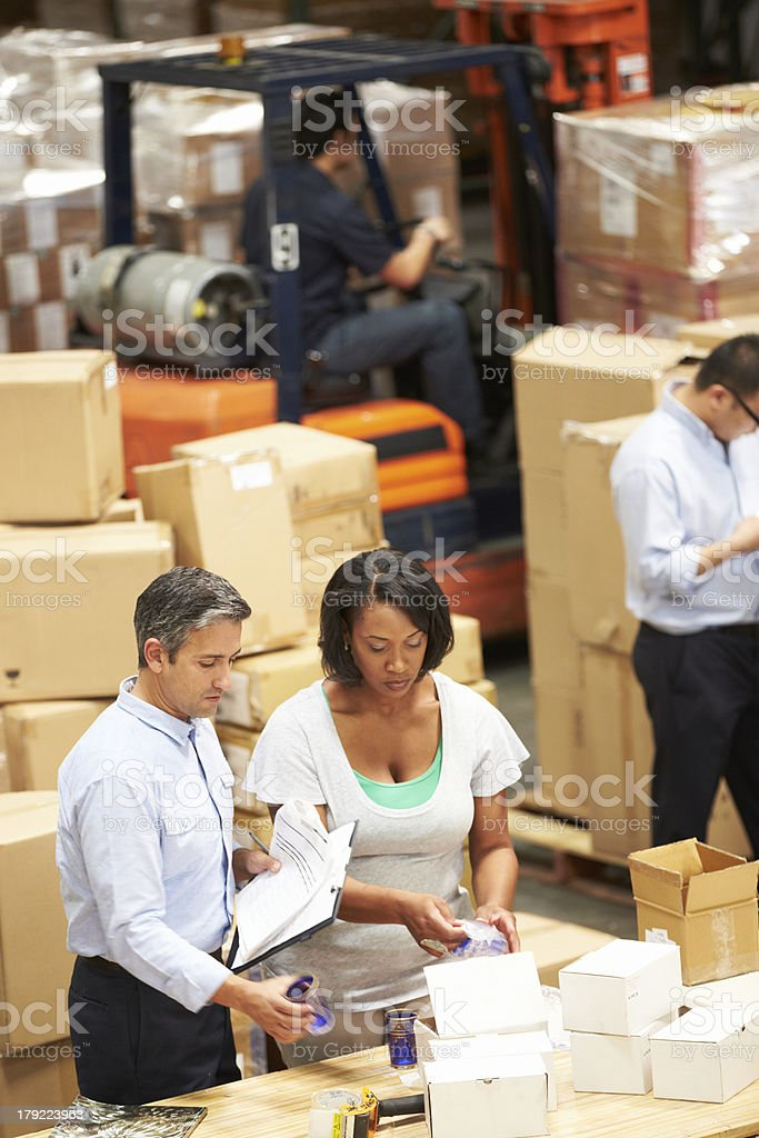 Workers in a warehouse talking stock photo