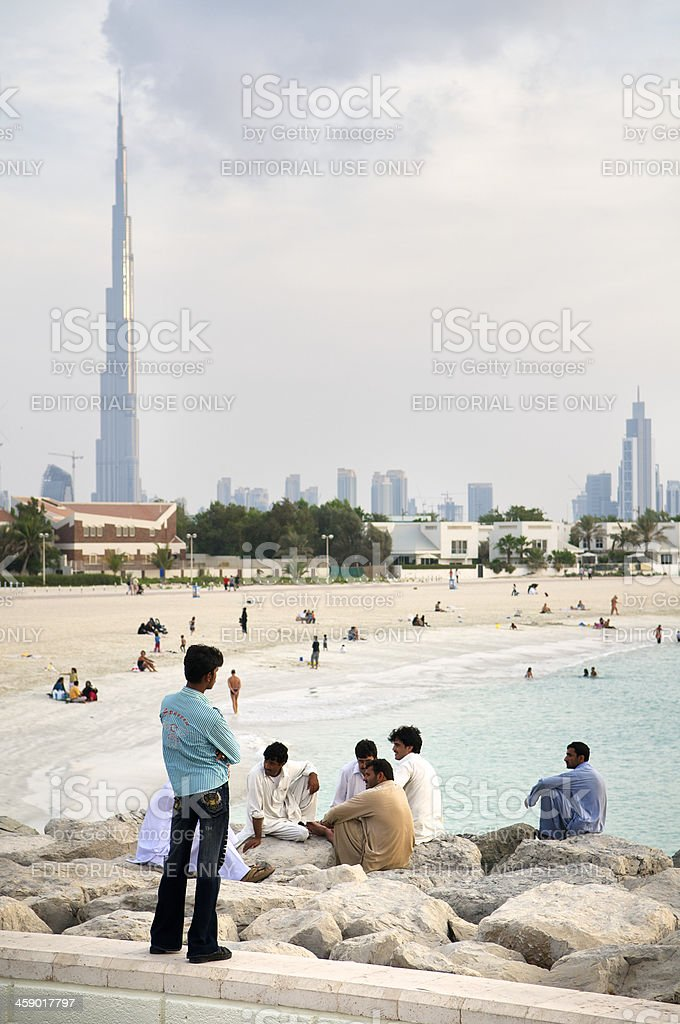 Workers in Dubai Relax at the Beach with City Skyline royalty-free stock photo