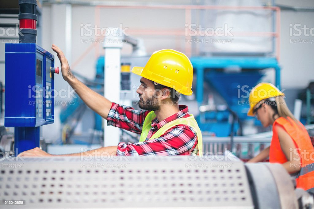 Workers in factory operating machines stock photo