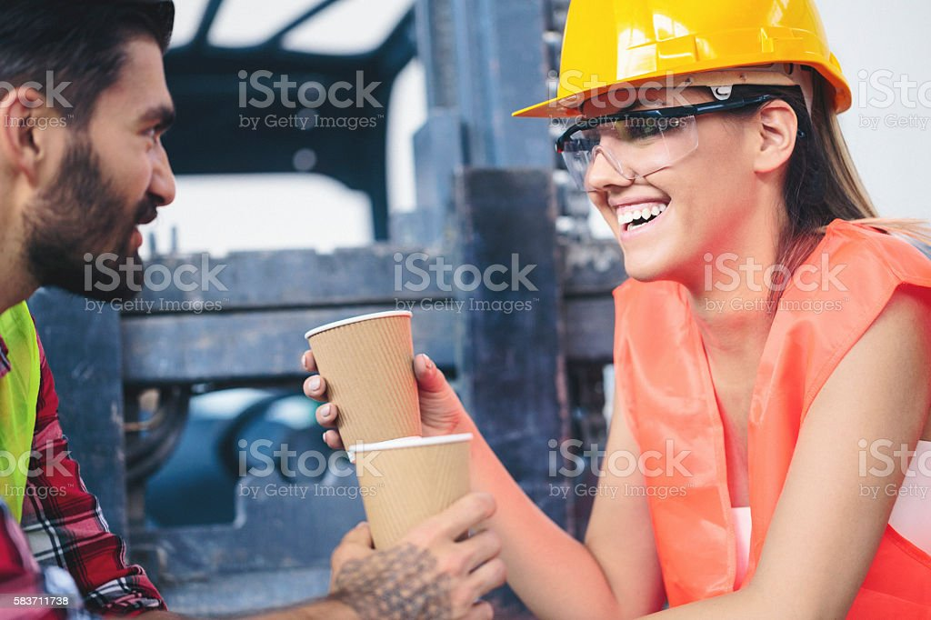 Workers in factory talking and having a coffee stock photo