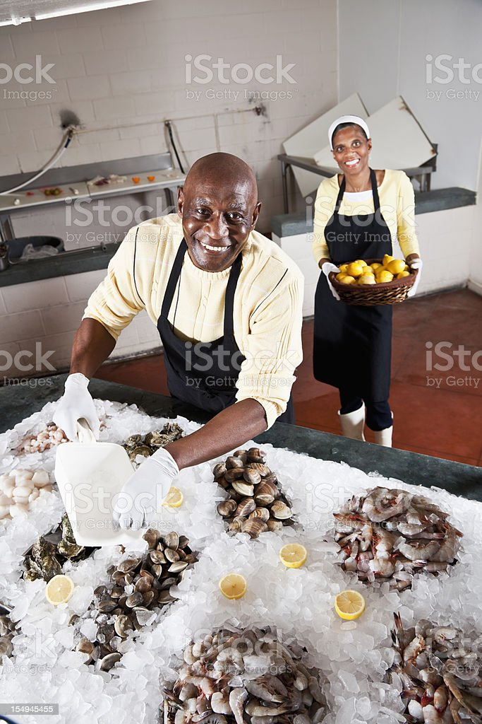 Workers in fish market arranging shellfish display stock photo
