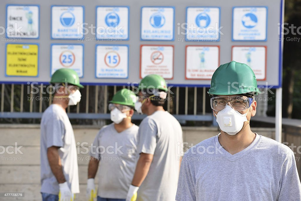 Workers in front of site safety notice stock photo