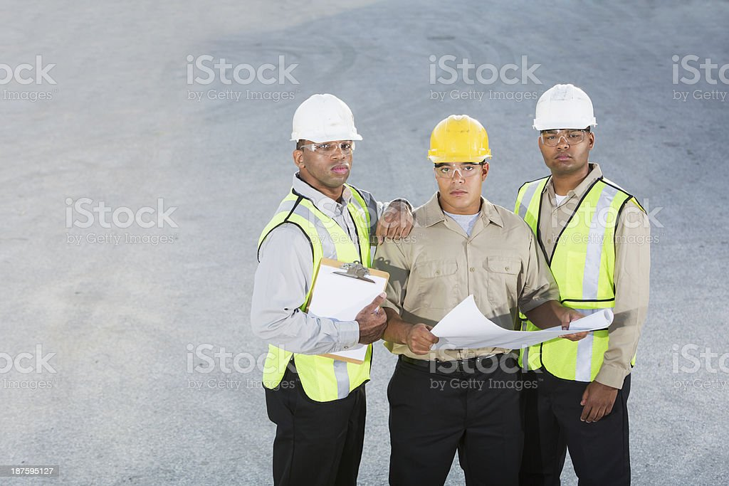 Workers in hardhats and safety vests royalty-free stock photo
