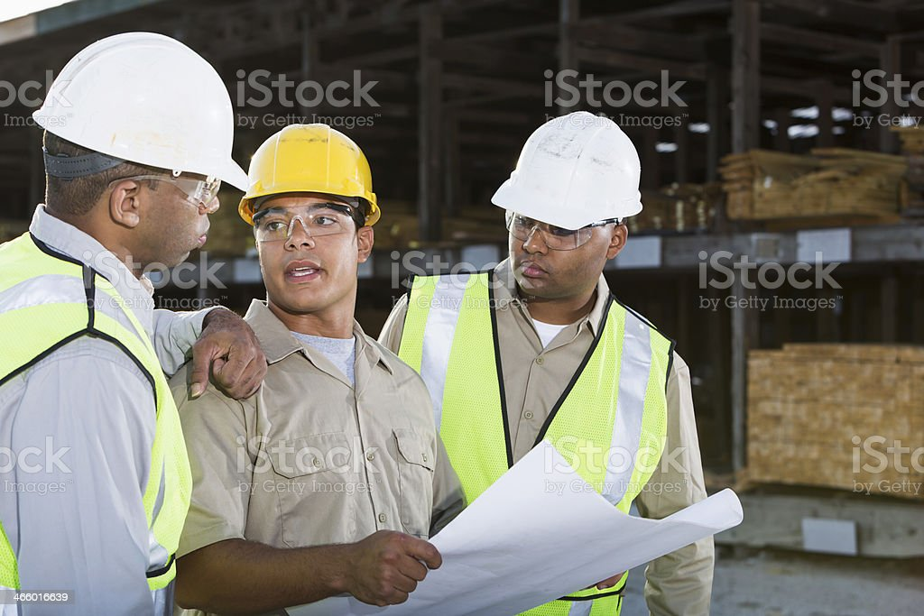 Workers in hardhats and safety vests stock photo