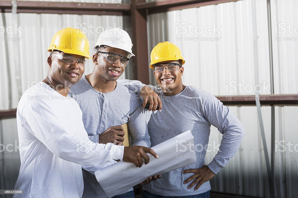 Workers in hardhats reading plans stock photo