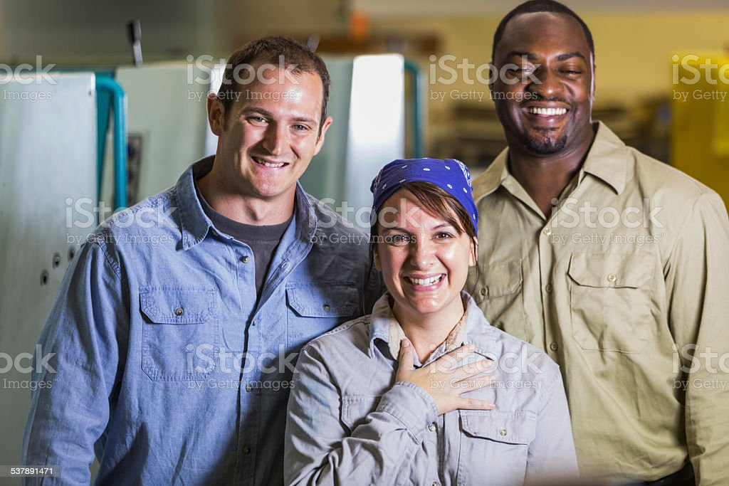 Workers in manufacturing plant standing by machines stock photo