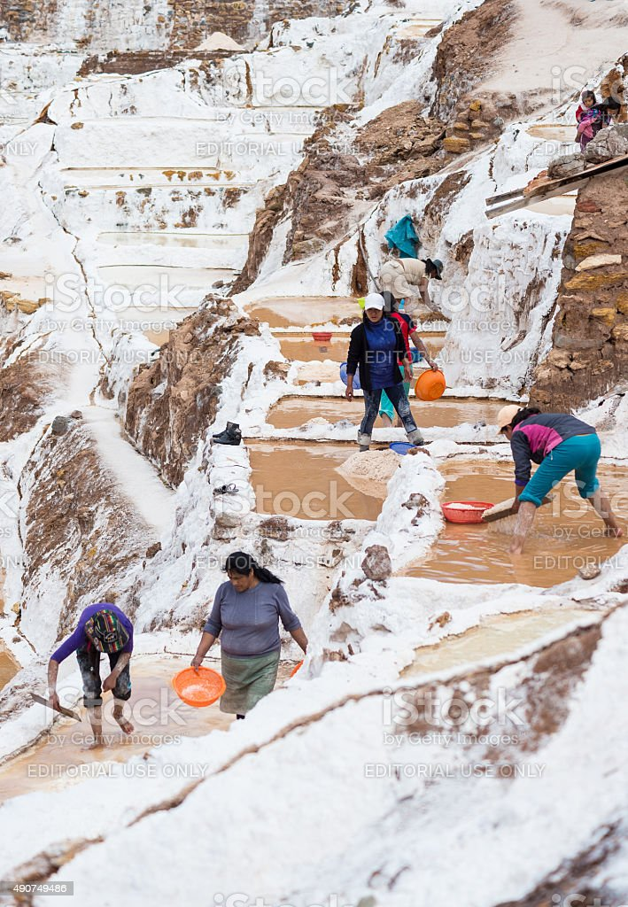 Workers in salt basins on the Peruvian Andes stock photo
