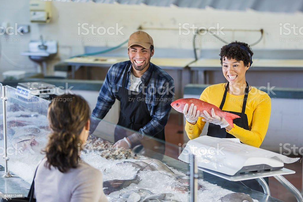 Workers in seafood market helping customer stock photo