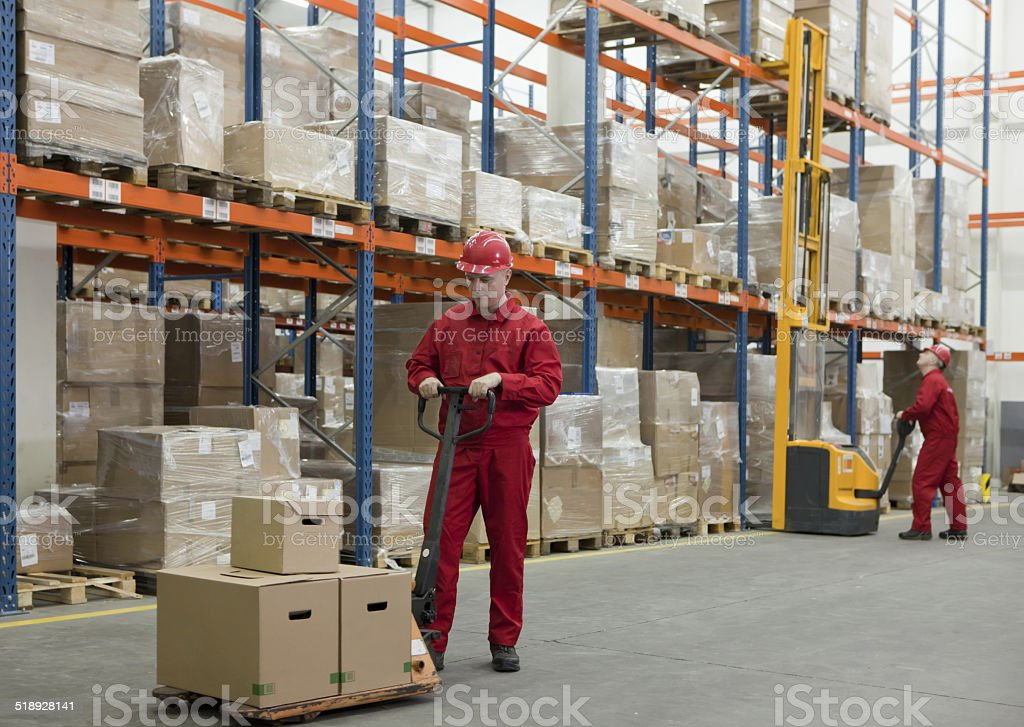 workers in uniforms and safety helmets working in storehouse stock photo
