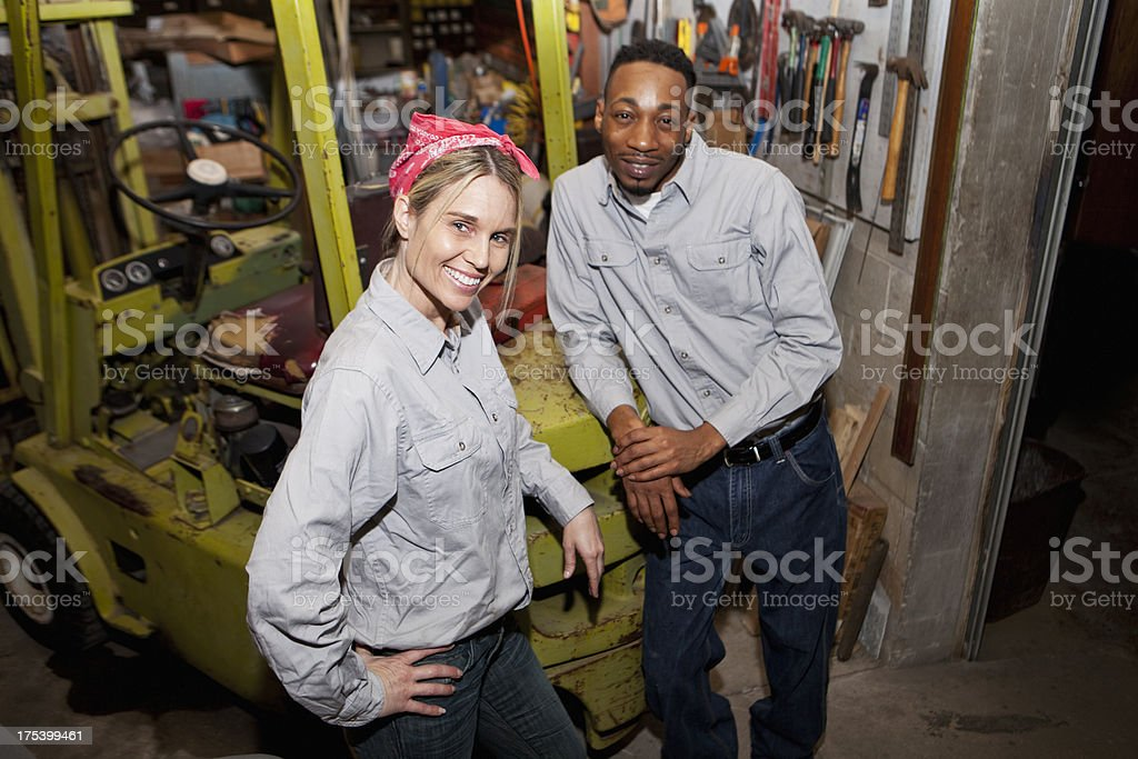 Workers in warehouse by forklift stock photo