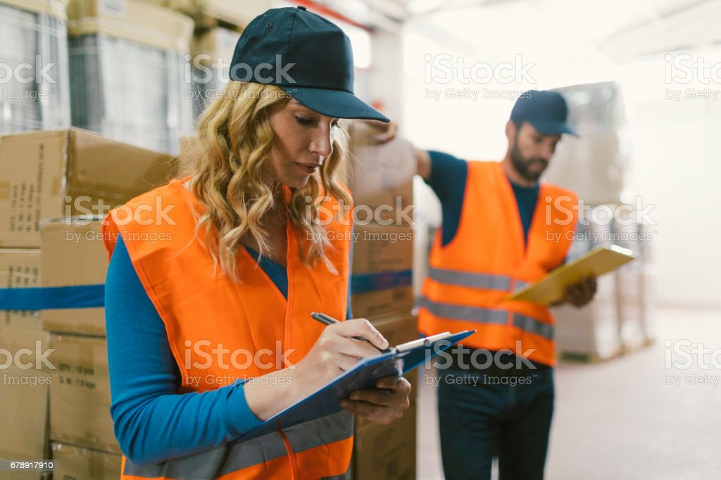 Workers in warehouse checking merchandise stock photo