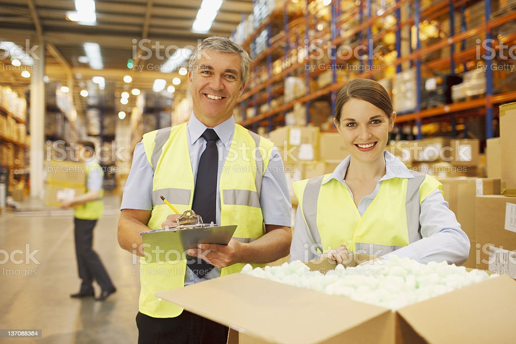 Workers in warehouse standing near box royalty-free stock photo