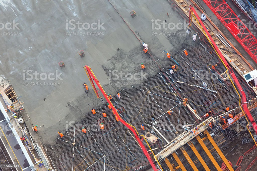 workers laying concrete - aerial view stock photo