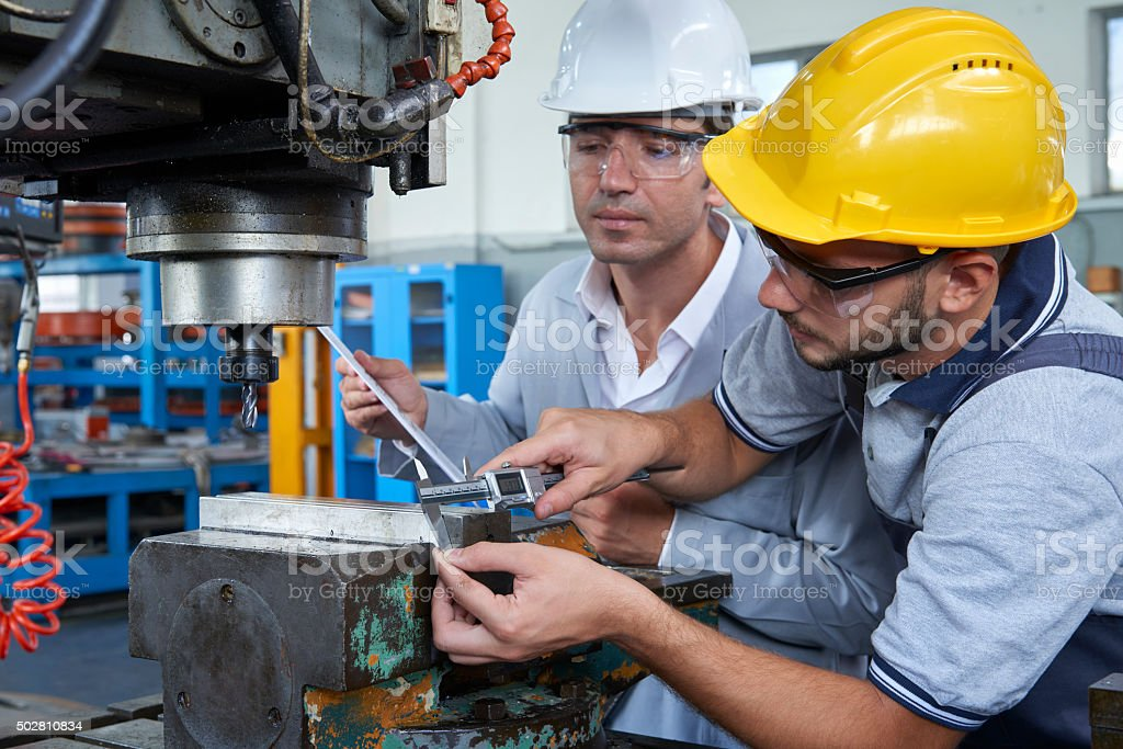 Workers measuring metal part in factory stock photo