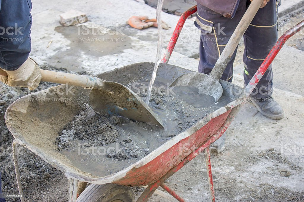 workers mixing the cement by hand in wheelbarrow 3 royalty-free stock photo