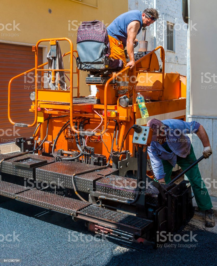 workers on a paver machine control the drafting of a new layer of asphalt for maintenance of city streets stock photo