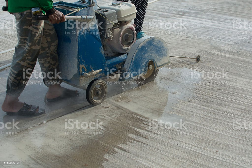Workers on a road construction use a blade cuting floor stock photo