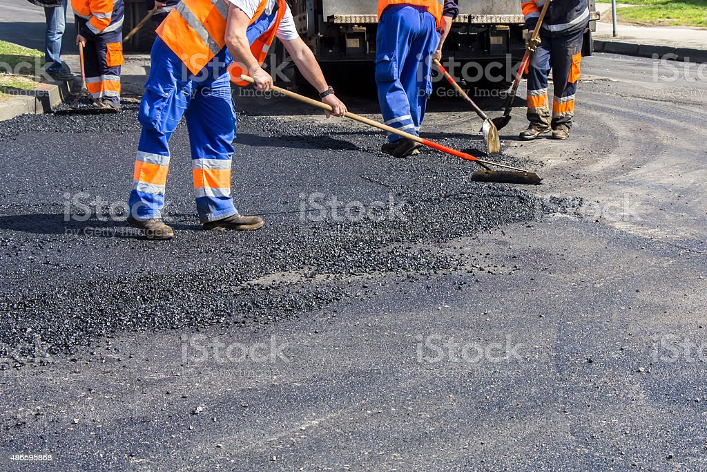 Workers on Asphalting road stock photo
