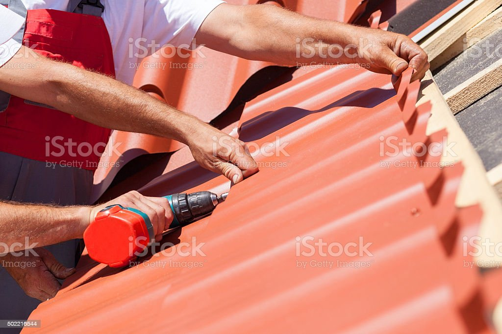 Workers on roof with electric drill installing red metal tile stock photo