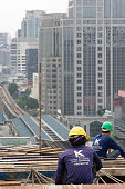 Workers on the top of a building site in Bangkok