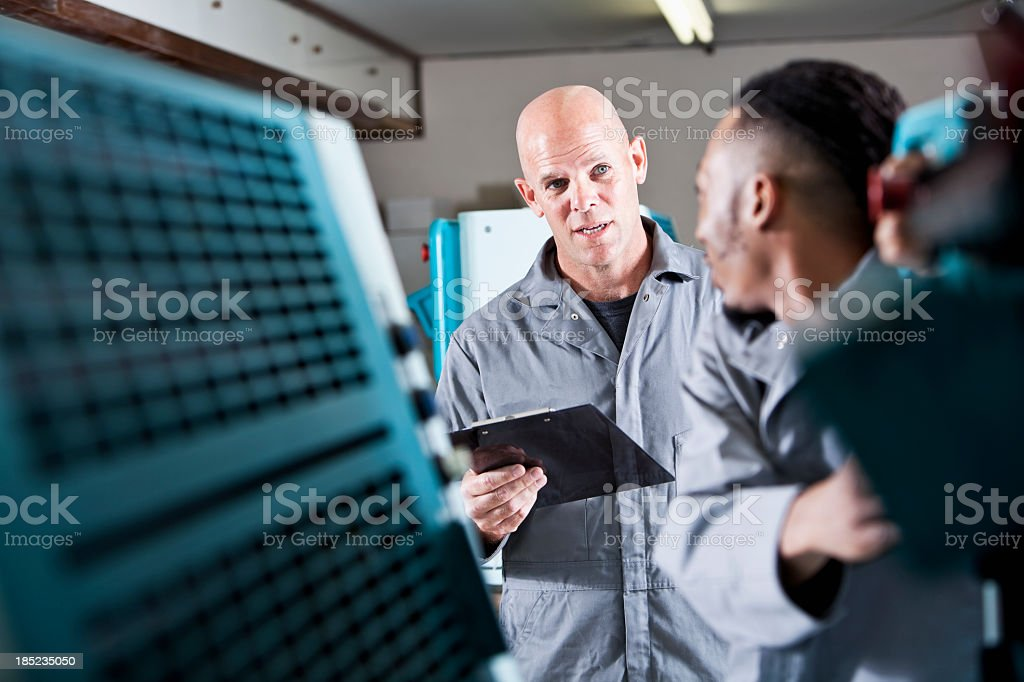 Workers operating printing press stock photo