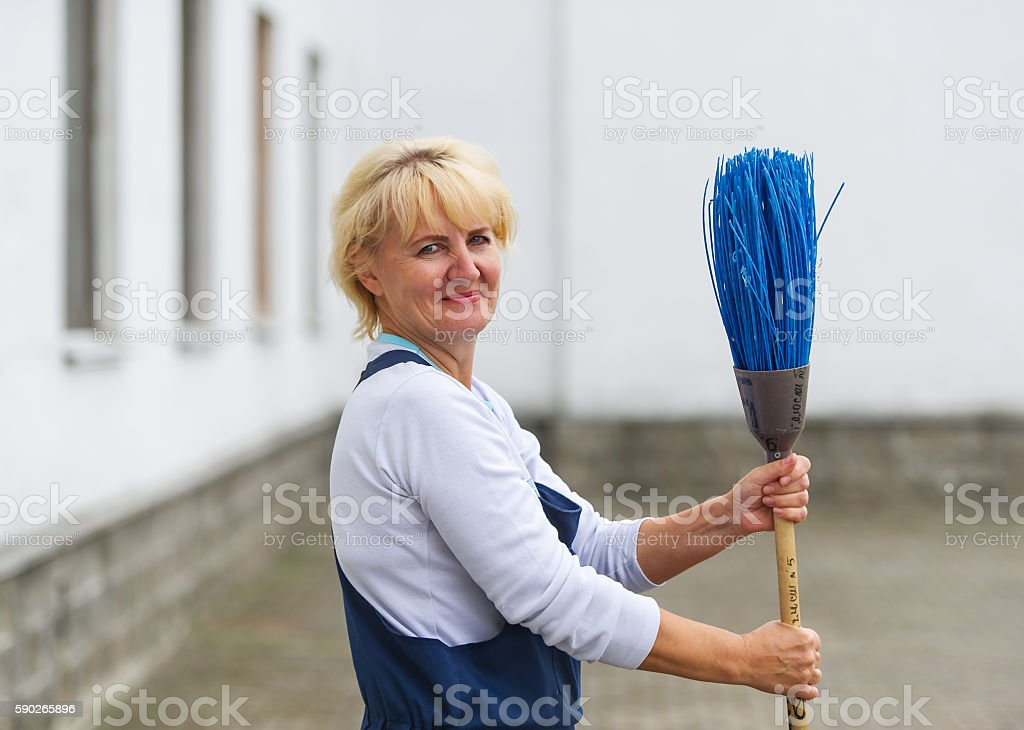 Worker's portrait cleaning city street with broom tool stock photo