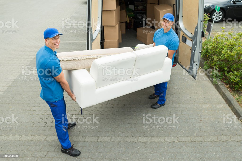 Workers Putting Furniture And Boxes In Truck stock photo