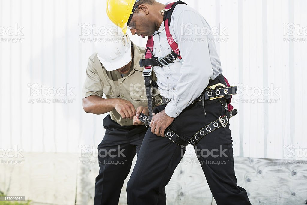 Workers, putting on safety harness stock photo