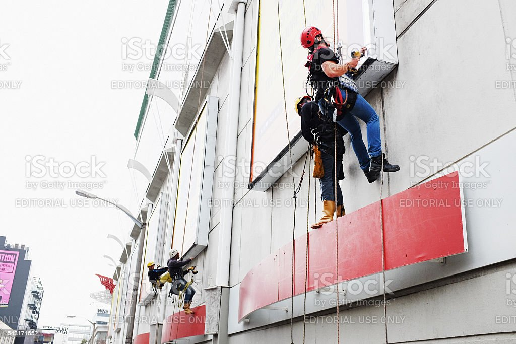 Workers rappelling down a shopping mall exterior to access billboards stock photo