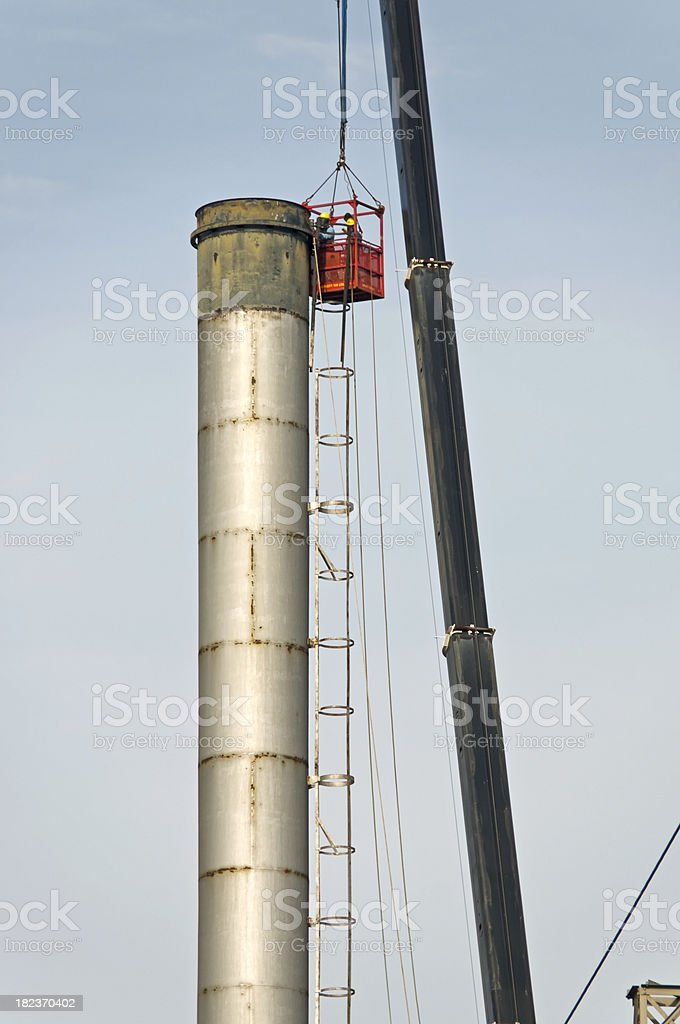 Workers removing ladder from smokestack of power plant royalty-free stock photo
