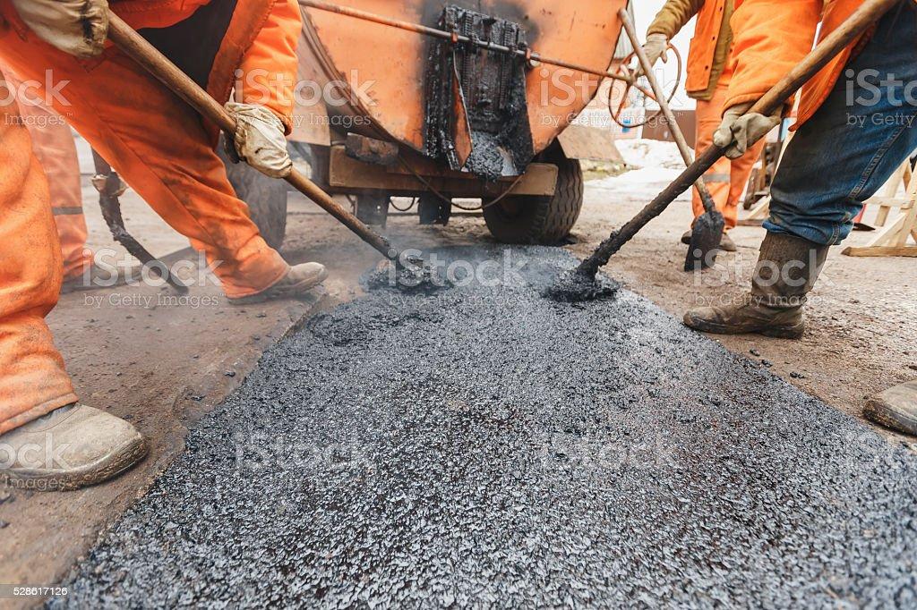 Workers repairing the road with shovels fill asphalt driveway repair stock photo