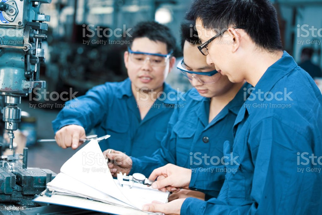 Workers reviewing blueprints in a factory stock photo