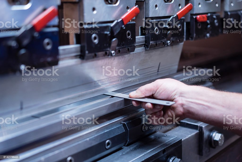 worker's right hand holding a metal plate stock photo