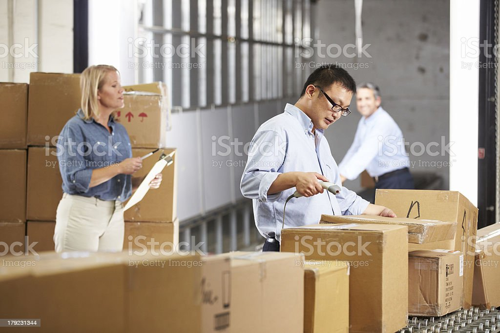 Workers scanning boxes on a belt at a warehouse royalty-free stock photo