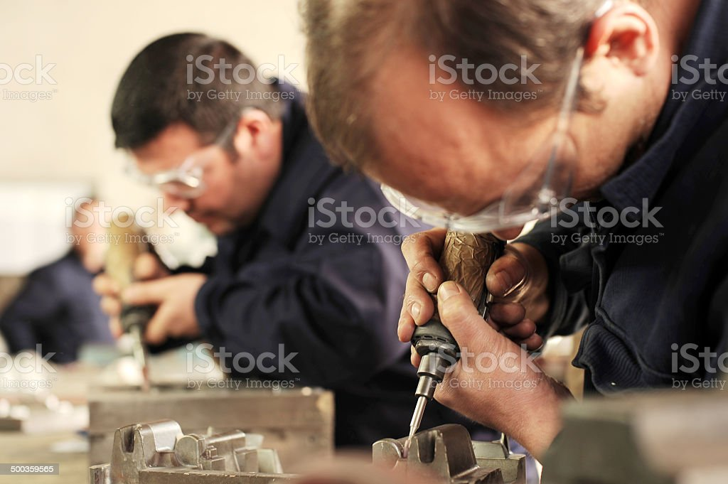 Workers shaping metal with tools royalty-free stock photo