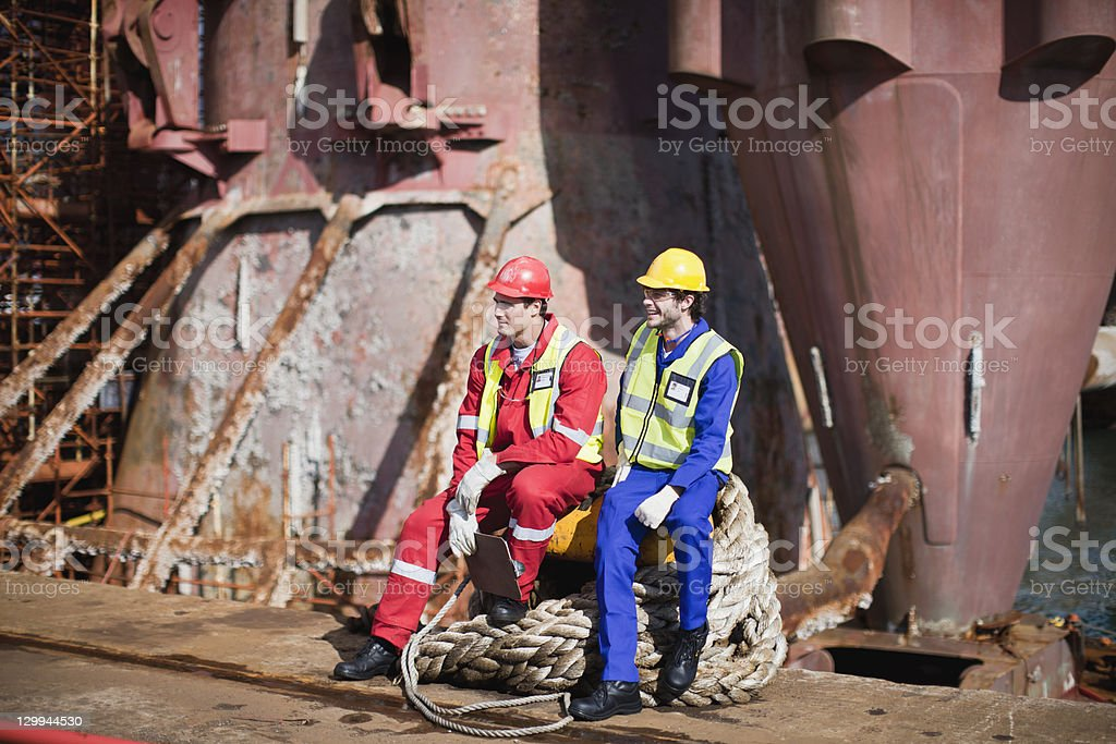 Workers sitting on rope on oil rig stock photo