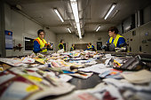 Workers sorting papers at recycling plant