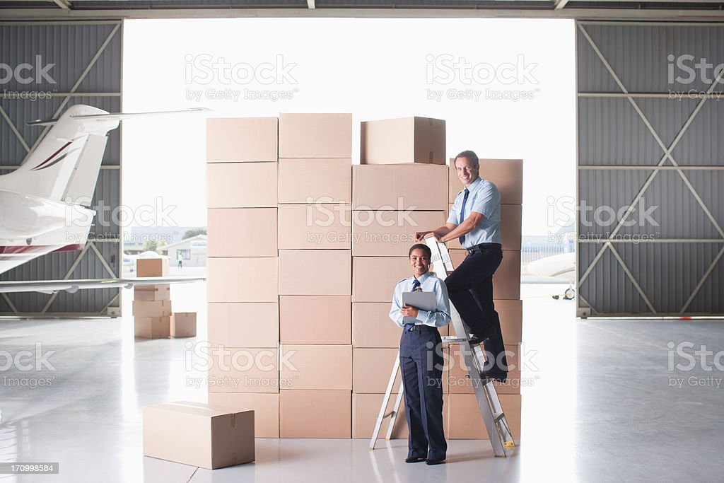 Workers stacking cardboard boxes in hangar royalty-free stock photo