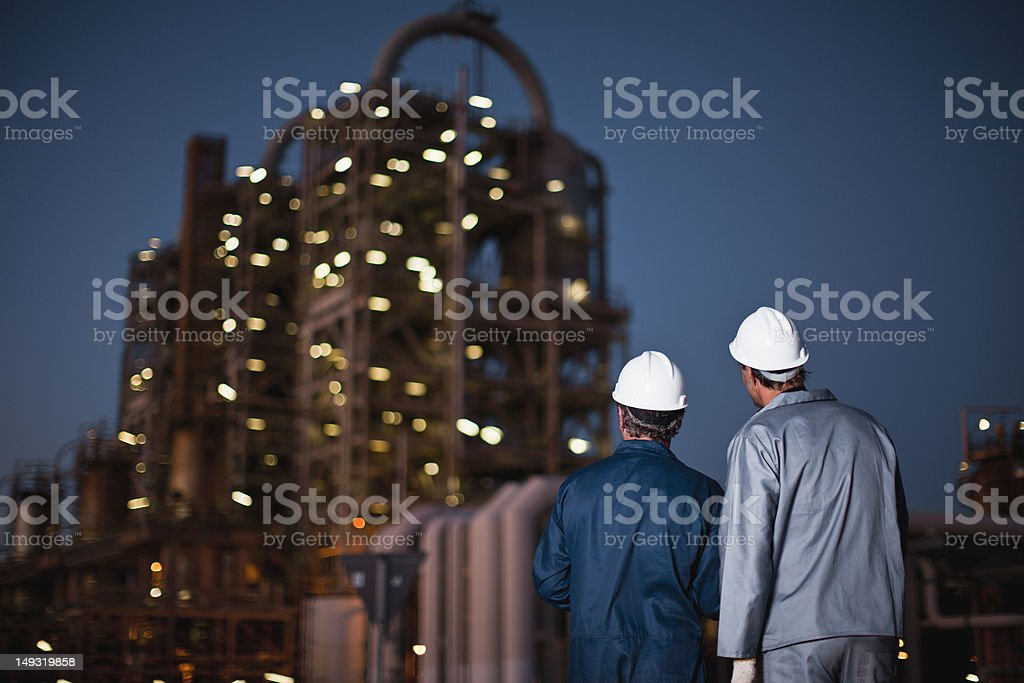 Workers standing at oil refinery stock photo