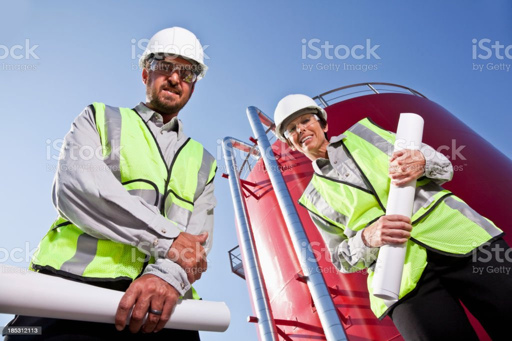 Workers standing by industrial water tower royalty-free stock photo