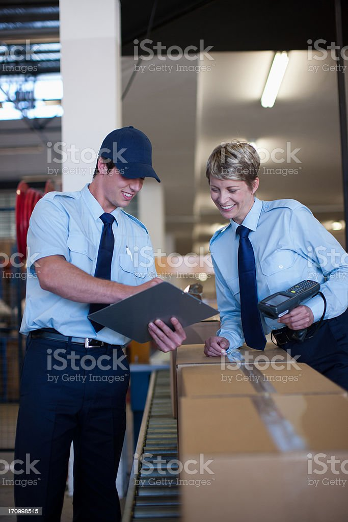 Workers standing together near box on conveyor belt stock photo