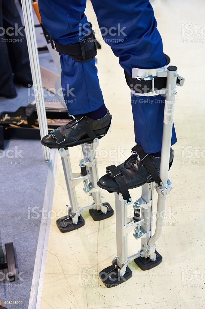 Workers stilts wearing on legs of men stock photo