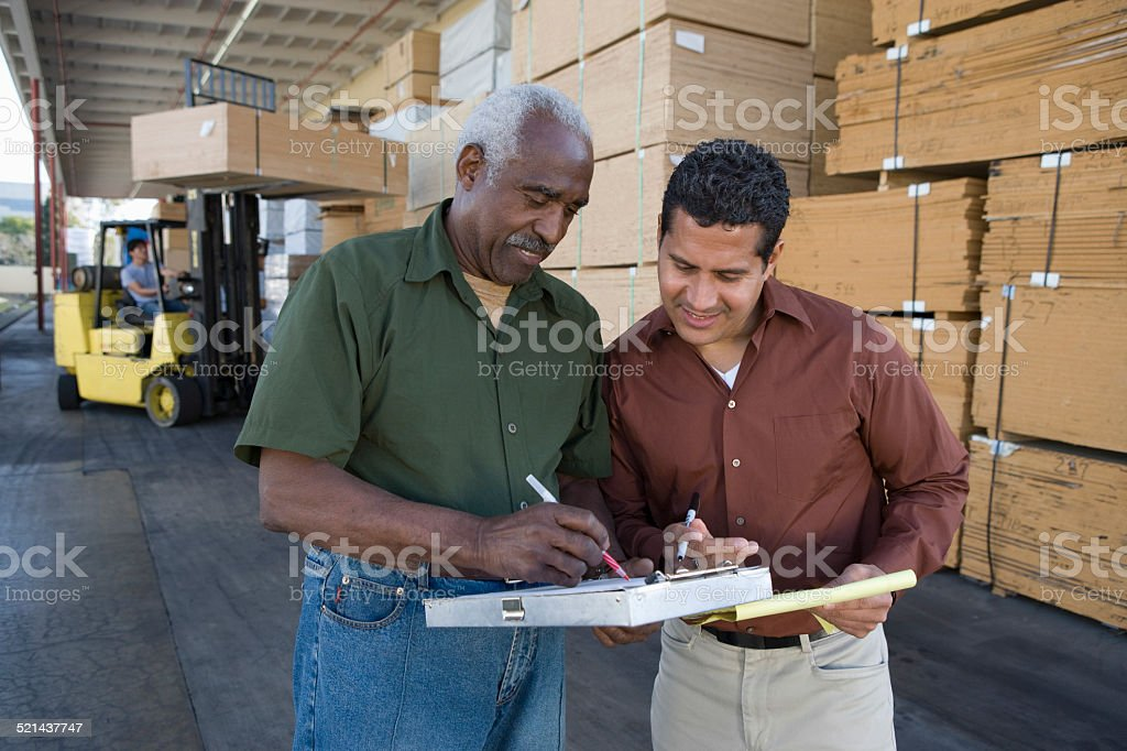 Workers Stocktaking In Timber Factory stock photo
