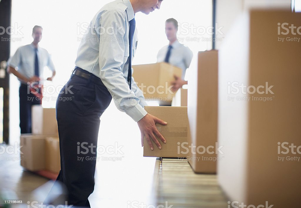 Workers taking boxes from conveyor belt in shipping area stock photo