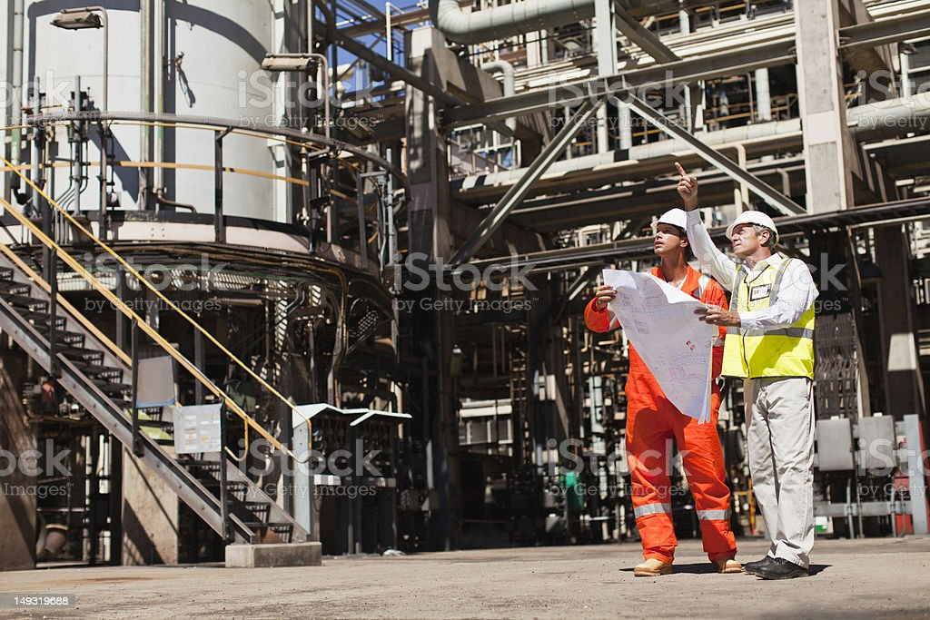 Workers talking at oil refinery stock photo