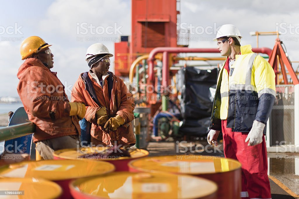 Workers talking on oil rig stock photo